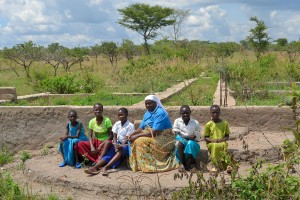 Sister Janepha, with girls from the village, pose together on the dormitory's foundation - their future school!